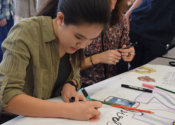 """Sophomore Sebrina Gao of Freehold responds to the prompt """"2016 in doodles"""" with the rest of her team for the Art Challenge. The sophomores finished first place in this event."""