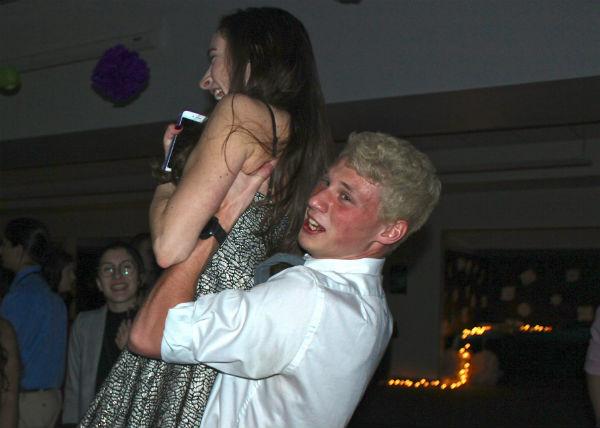 Senior Matt Miller of Wall picks up senior Anna Soltys of Holmdel in excitement during an upbeat song.