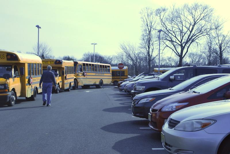 After school the parking lot is filled with buses and students trying to leave in their cars.