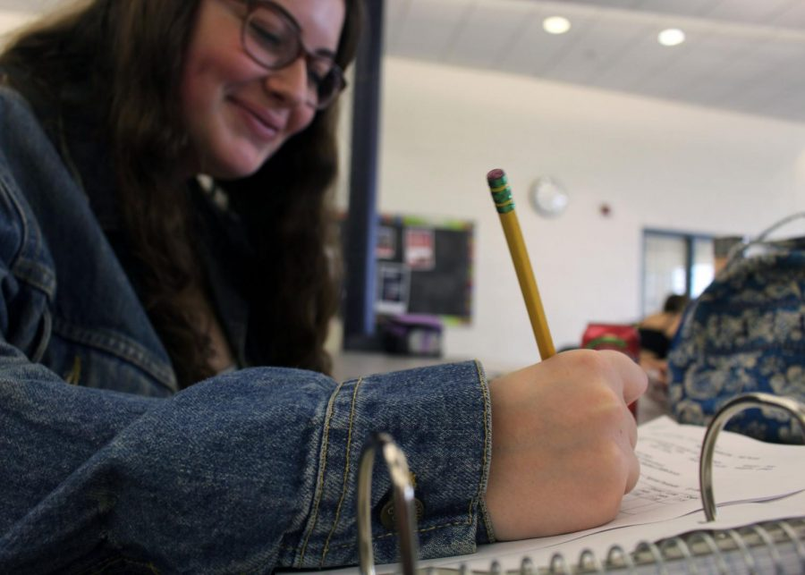 During lunch, junior Tali Petto of Marlboro rushes to finish a chemistry assignment. She has chemistry third period with teacher Erin Wheeler.
