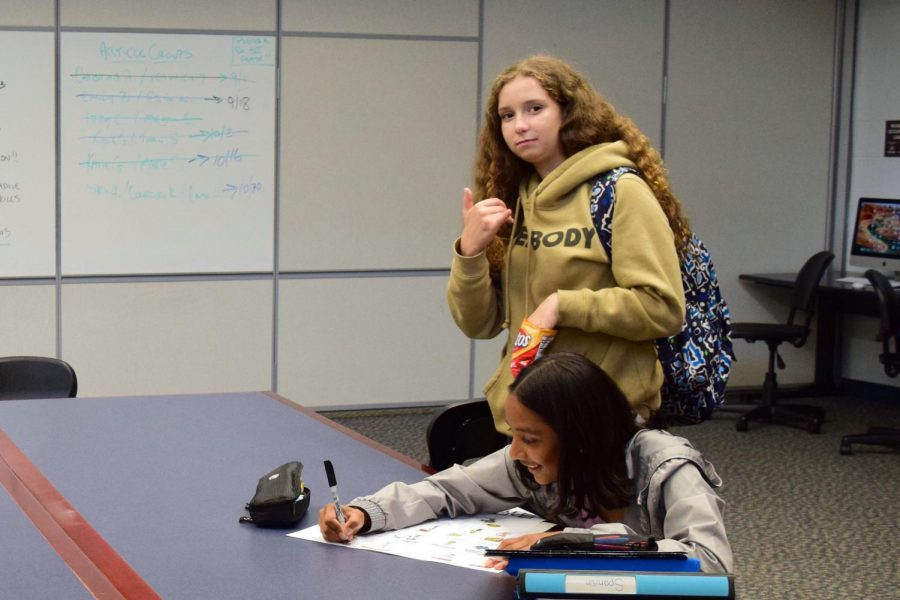 """Freshman Meg Ellis of Freehold takes a break from her Spanish I project to pose and offer some """"Shaka"""" vibes to the Inkblot."""