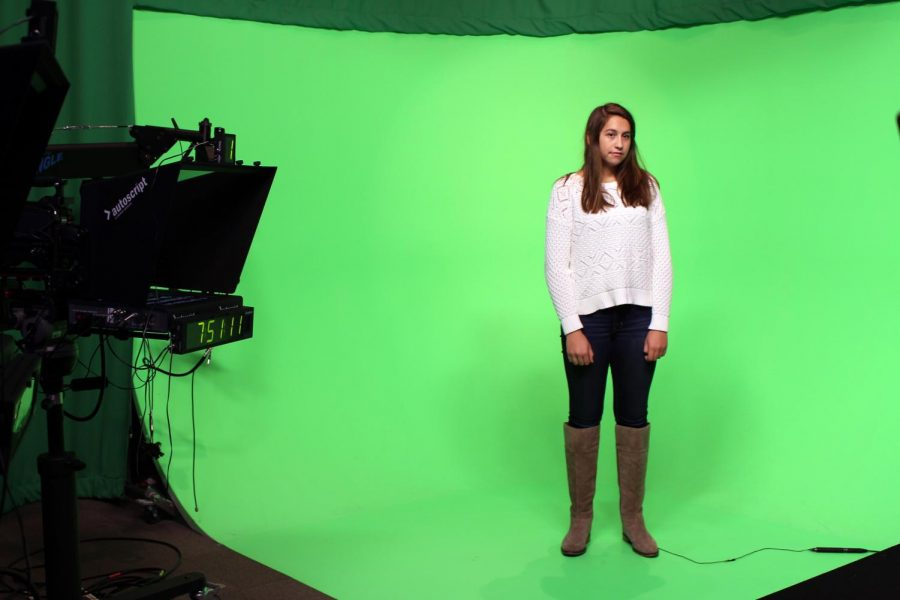 """One hour and six minutes before CHS' morning news show, """"Views From the Studio"""", begins its broadcast, junior Kate Dickenson of Spring Lake stands in front of the green screen to record the weather segment."""
