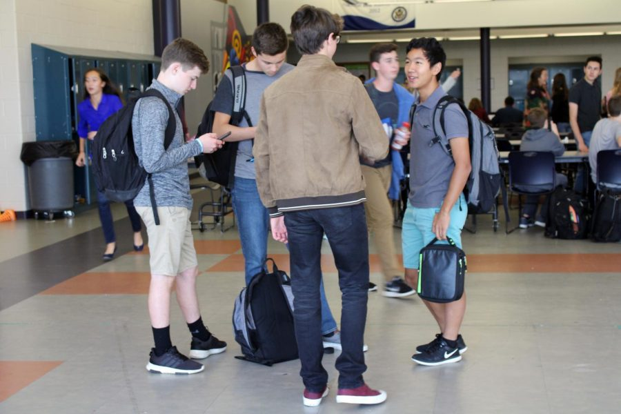 Before they part ways for third period, sophomores, from left, Joe Matthews of Middletown, Ben Hewson of Fair Haven, Sawyer Barth of West Long Branch and Evan Kuo of Tinton Falls group together in the back of the cafeteria. Barth and Kuo say hello to each other before they join their friends and pull out their phones.