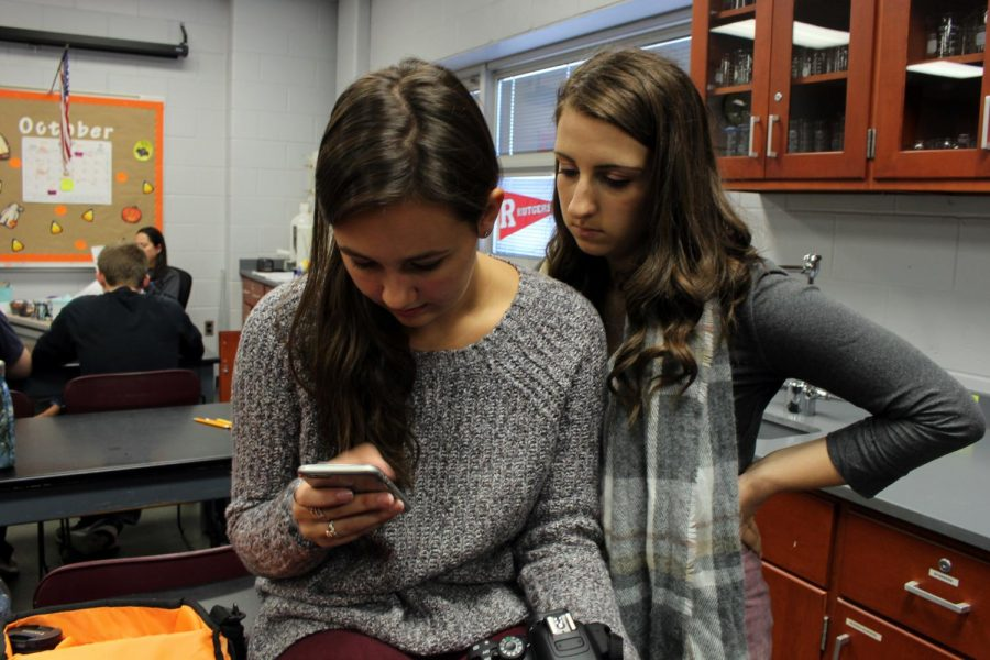 Waiting for the third period bell to ring, juniors Allie Beekman of Neptune and Jules Andersen of Howell chat and look at Allie's phone. The class had a test today on covalent bonds.