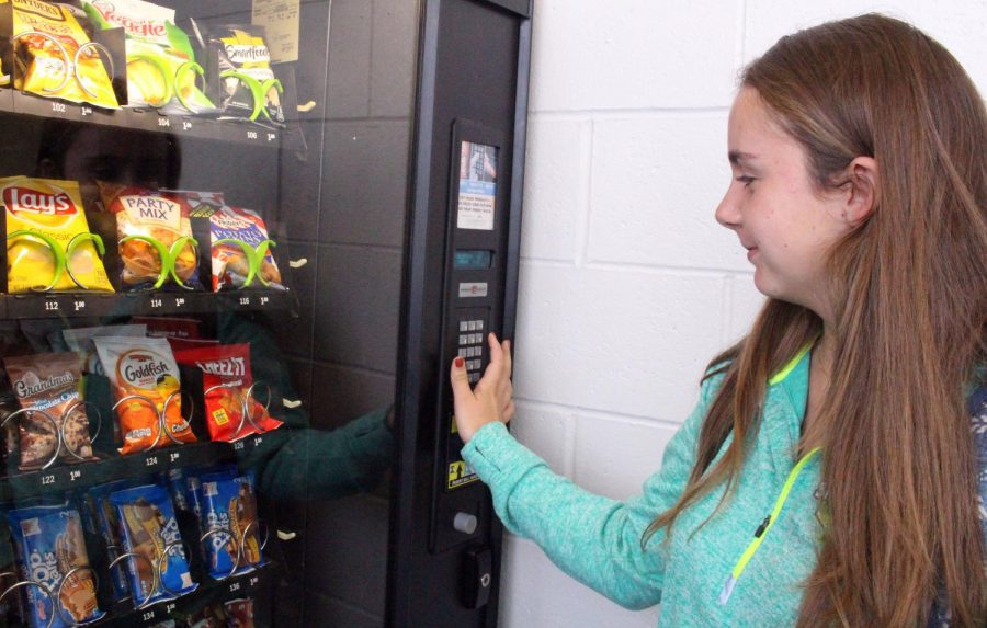 After a long morning of classes, junior Grace Treshock of Monmouth Beach is excited to get a snack from the vending machine. Luckily the vending machine had Cheez-its today, which are her favorite.