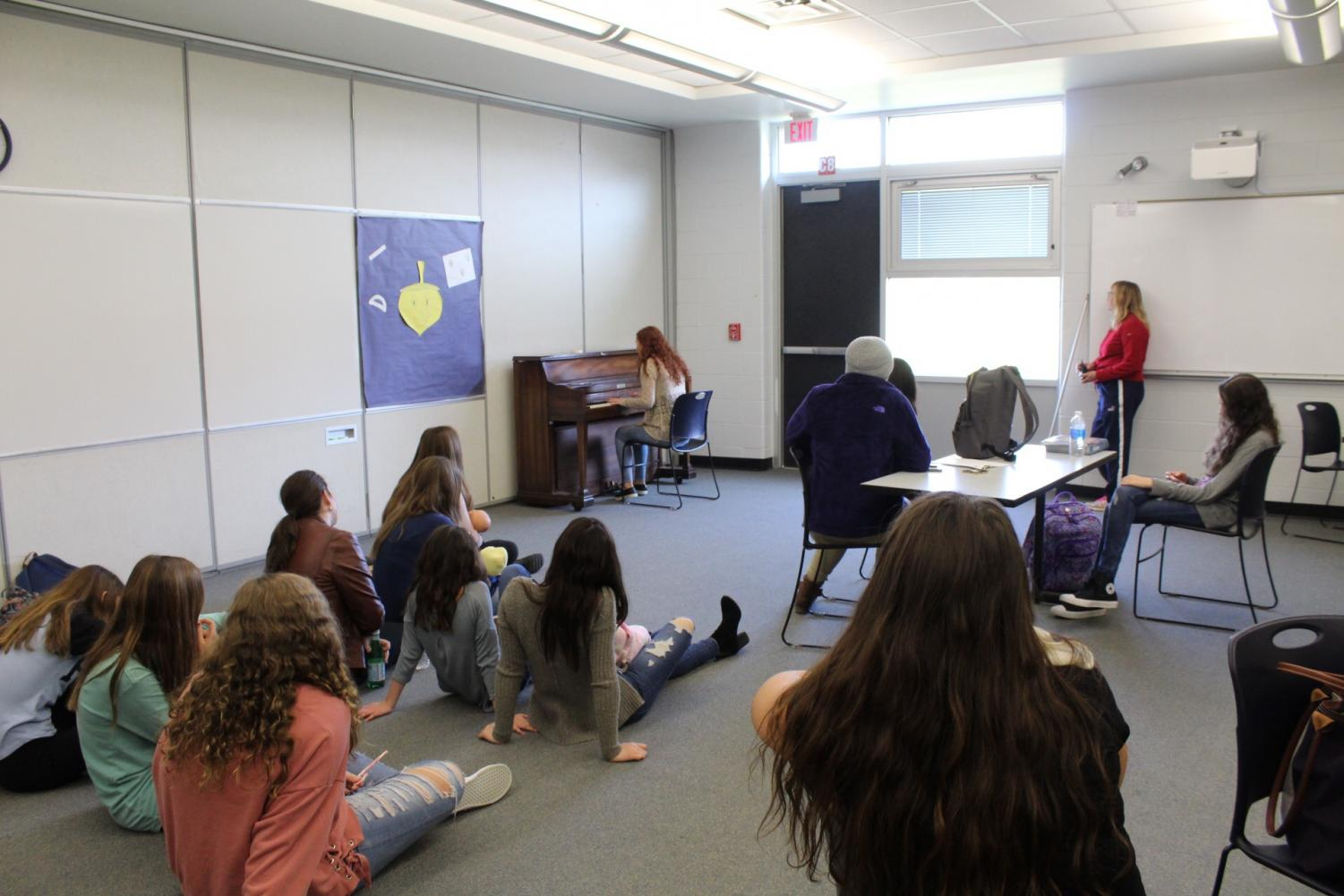 Students who attend Musical Mindful Mondays sit on the floor to listen to their classmates.