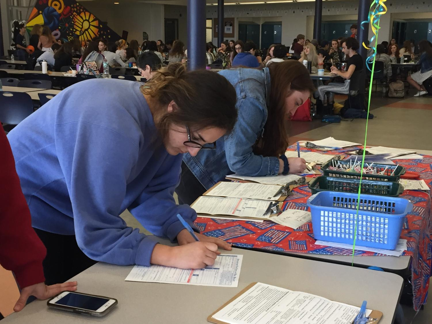Seniors Courtney Kushnir of Colts Neck and Shannon Damiano of Spring Lake Heights fill out voter registration forms.