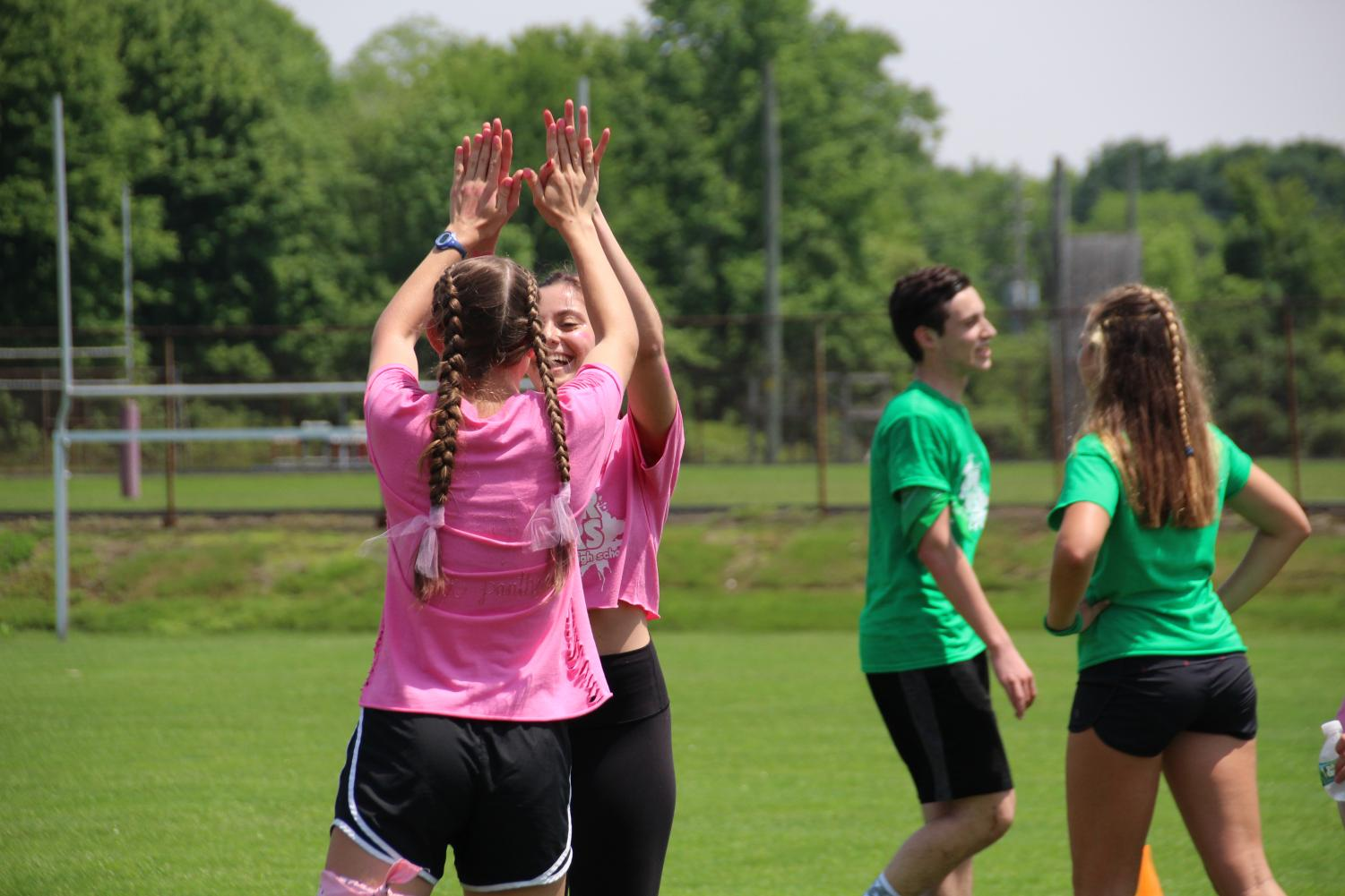 Pink+Team+captain+and+senior+Izzy+Cavazzoni+of+Wall+and+junior+Erica+Sammarco+of+Colts+Neck+high+five+after+a+victory+in+soccer.+The+Pink+Team+placed+third+overall+in+the+event.