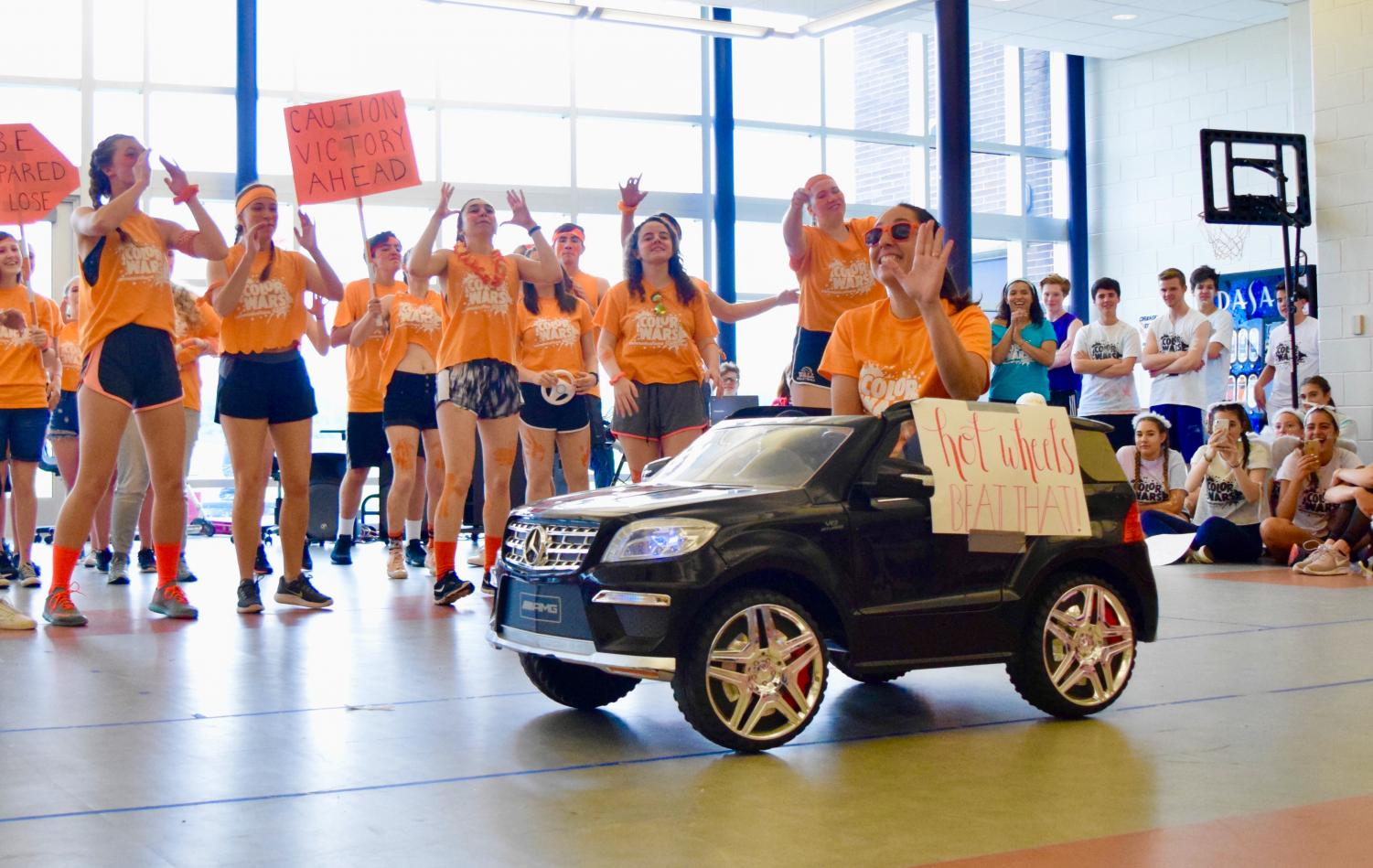 As+a+way+to+incorporate+their+team+name+of+%E2%80%9CHot+Wheels%2C%E2%80%9D+Orange+Team+adviser+and+chemistry+teacher+Erin+Wheeler+rides+a+miniature+car+at+the+end+of+the+team+chant.+