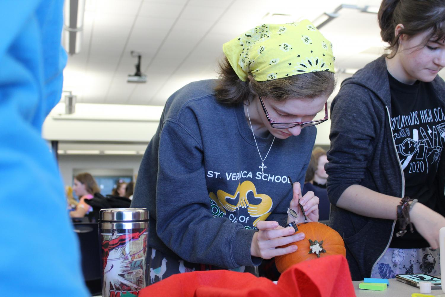 Junior Emily Madeira of Howell draws on one of the Class of 2020's pumpkins for the Pumpkin Decorating competition.