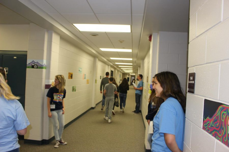 Sophomore, junior and senior students line the back hallway to direct prospective students and their families to the cafeteria.