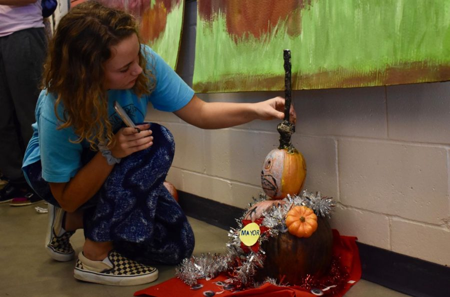 Sophomore Brigid McCarthy of Manasquan adjusts the Class of 2021's pumpkin display in front of the Fall Spirit Week scoreboard.