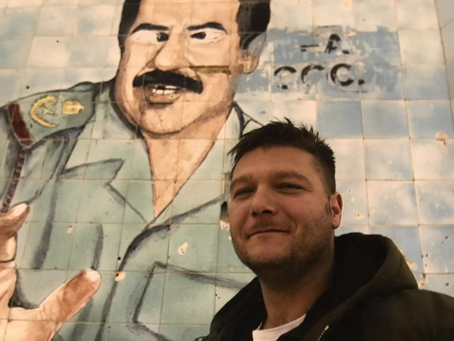 Woolley poses in front of a defaced mural of Saddam Hussein in Baghdad while covering the Iraq War in 2005.