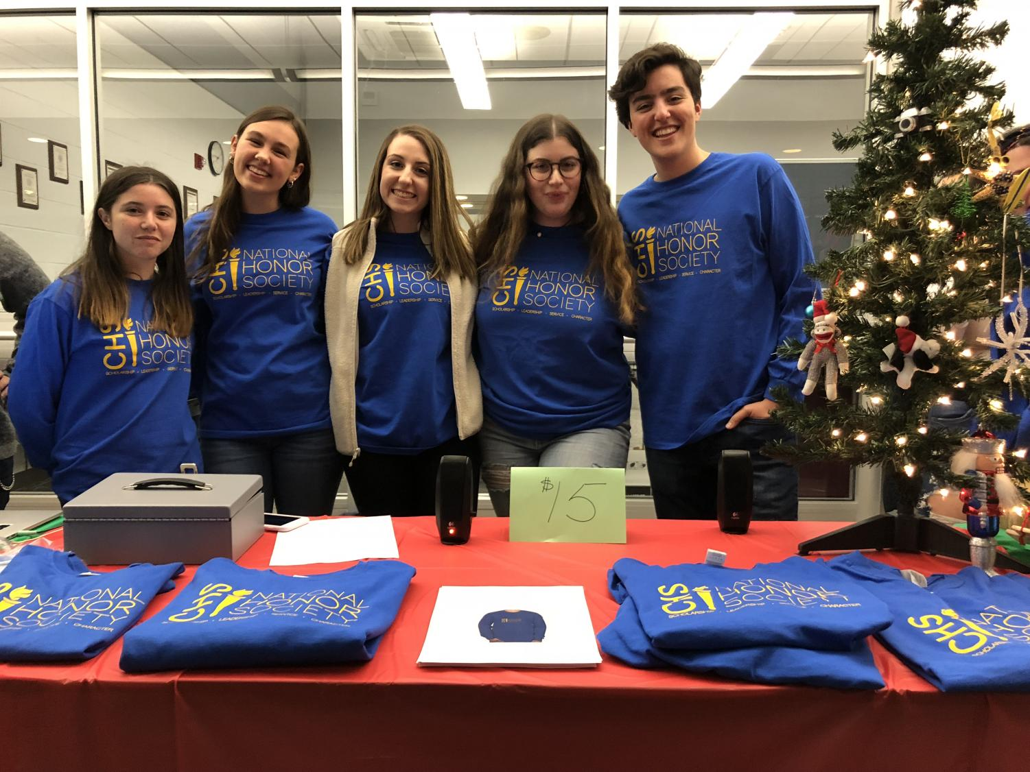 Seniors and NHS members, from left, Emma Farkas of Colts Neck, treasurer Allie Beekman of Neptune, president Jules Andersen of Howell, secretary Tali Petto of Marlboro and Liam Marshall of Sea Girt represented the National Honor Society (NHS) at Mingle & Jingle. NHS sold t-shirts and played Christmas music at the event.