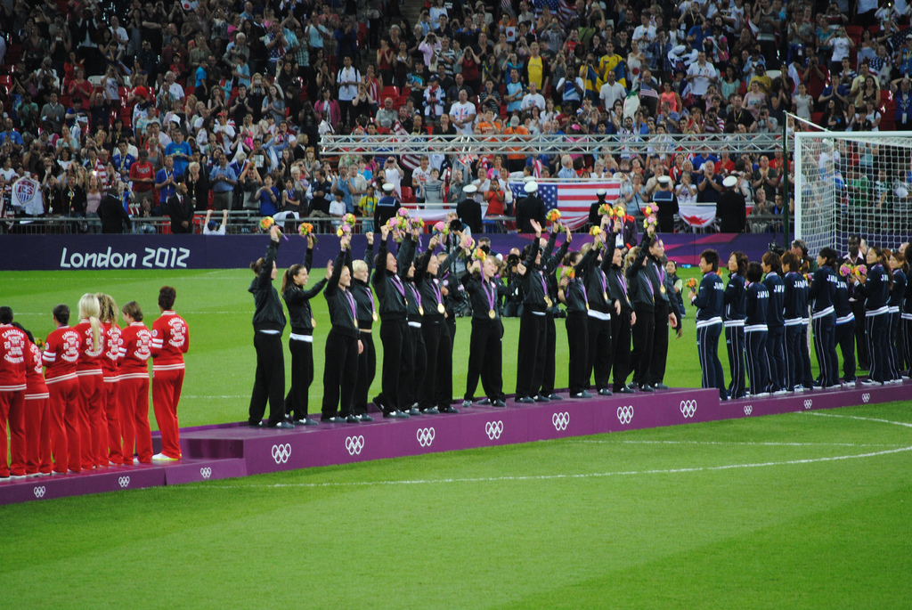 The US Women's National Team, center, raises their gold medals at the 2012 Olympics. https://creativecommons.org/licenses/by/2.0/