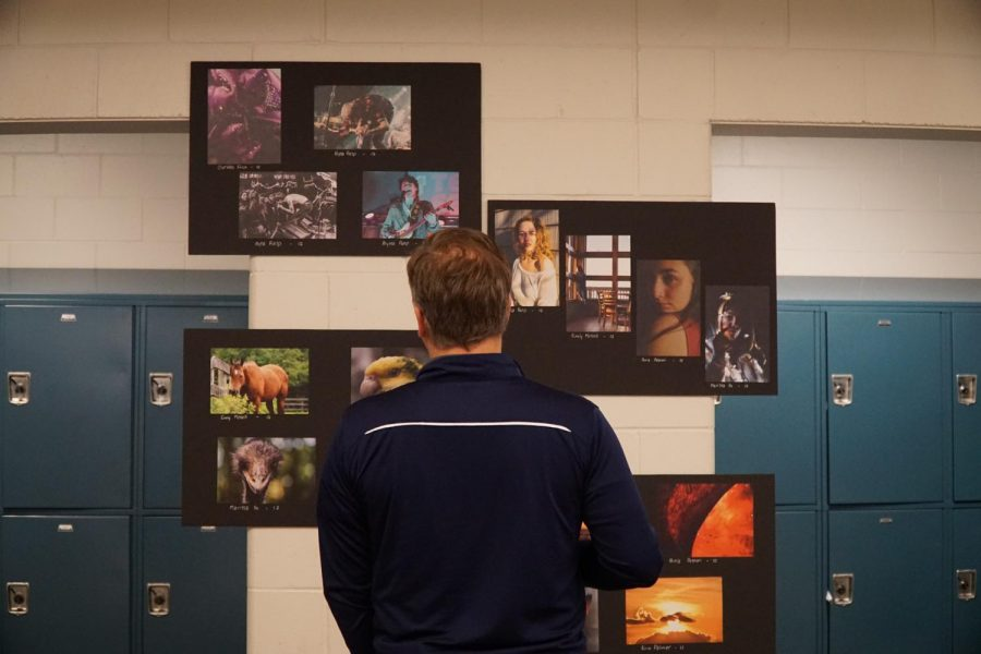 Principal James Gleason looks at student work showcased at the NAHS Art Show.