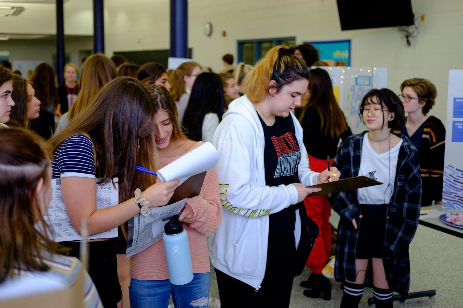 Students sign up for clubs that had stands in the cafeteria on Friday the 13th.