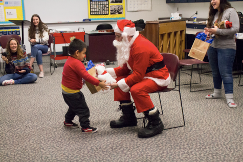 Physics teacher Steve Godkin, dressed as Santa, hands a Head Start student his present on Friday, Dec. 13. Godkin was the special surprise, along with other performances at the event.