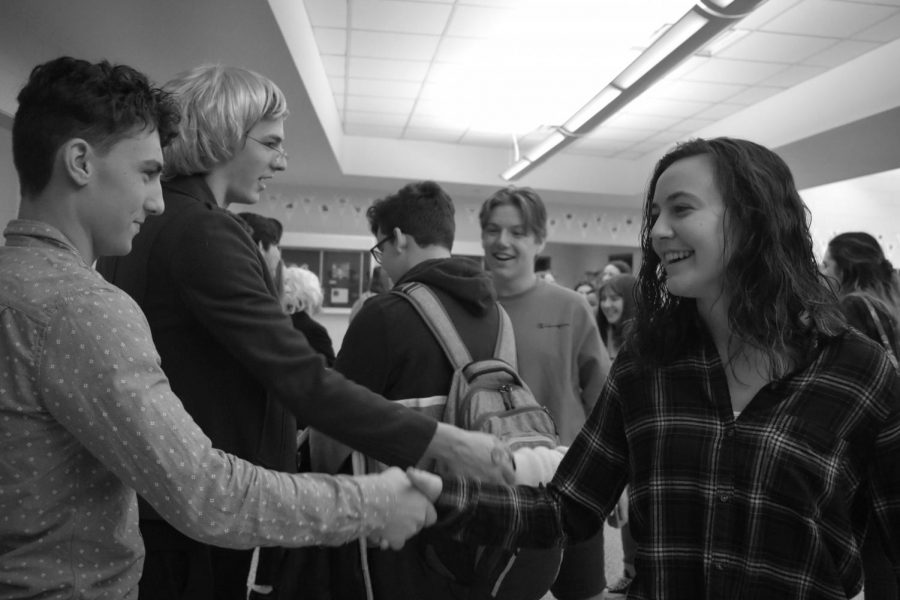 """JSA Mock Primary Debate candidates """"Joe Biden"""" and """"Elizabeth Warren,"""" portrayed by senior Colin Martin of Middletown and freshman Joey Esposito of Tinton Falls, respectively, shake hands with students."""