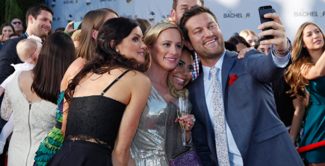 "Cast members of ""The Bachelor"" pose at a red carpet event."
