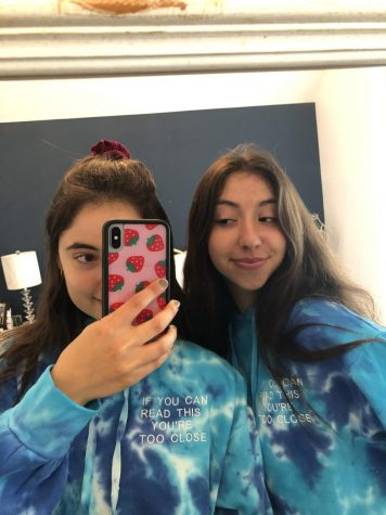 Senior Emma Barofsky, right, poses in her self-designed sweatshirts with her sister, Julia Barofsky. Profits from sweatshirt sales were donated to the CDC Foundation.