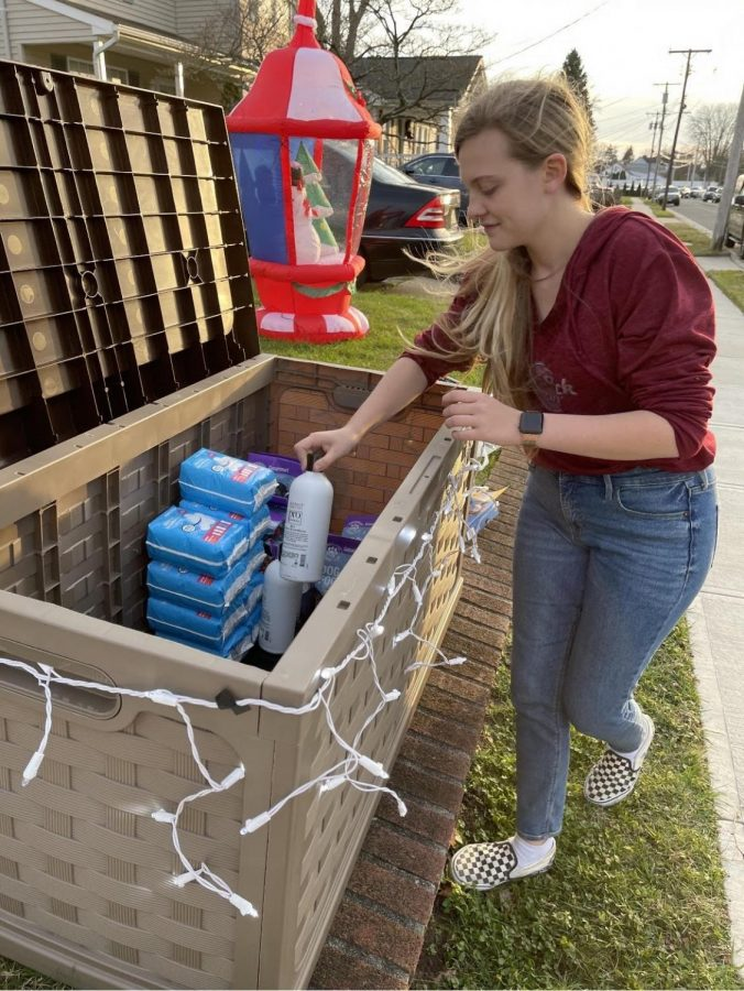 """Jodry places a shampoo bottle in """"The Giving Box,"""" a donation pick up and drop off service that she and her family run outside of her house."""